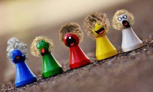 Das Bild zeigt fünf bunte Spielsteine mit aufgeklebten Gesichtern und Perücken.
