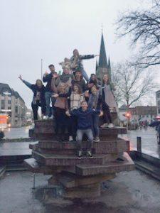 Eine Studierendengruppe der Orientierungswoche positioniert sich auf einem zentralen Denkmal in Paderborn